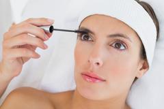 Hand applying mascara to beautiful woman Stock Photos