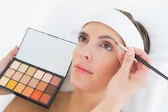 Hand applying eyeshadow to beautiful woman - stock photo