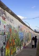 Couple walking along the East Side Gallery Berlin Wall mural, Berlin, Germany Stock Photos
