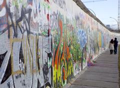 Couple walking along the East Side Gallery Berlin Wall mural, Berlin, Germany Stock Photos