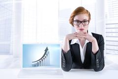Stock Illustration of Composite image of redhead businesswoman sitting at desk