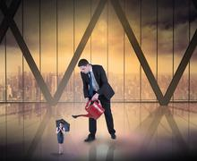 Composite image of businessman watering tiny businesswoman - stock illustration