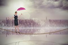 Stock Illustration of Composite image of pretty redhead businesswoman holding umbrella on tightrope