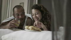 Happy attractive couple relaxing in the bedroom Stock Footage
