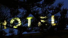 Yellow neon hotel sign as seen from through a pine tree Stock Footage