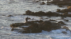 4K Man walking on rugged rocks by the beach while waves crash Stock Footage