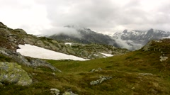 Cold rainy evening in high Alpine mountains, snowy blue peaks below dark clouds - stock footage