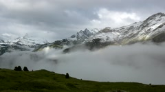 Silhouettes of high Alpine mountains sticking out from heavy mist clouds Stock Footage