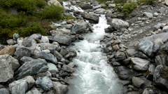 Rapids on quick mountain torrent in Alps, water is flowing over white boulders - stock footage