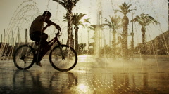 Young boys on bikes cooling off in fountain in the city in summertime - stock footage