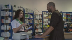 Patient receiving from pharmacist drug tablet from prescription paper shop scene - stock footage