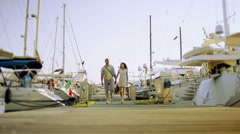 Attractive romantic couple looking at the boats in the harbour Stock Footage