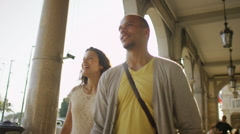 Happy attractive couple walking together in the city in the summertime - stock footage