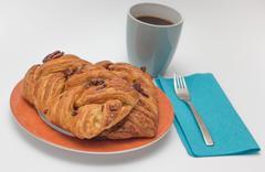 Sweet pecan bun and a cup of black coffee Stock Photos