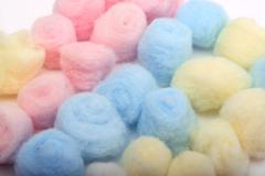 Yellow, blue and pink hygienic cotton balls in rows - stock photo
