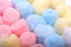 Blue, yellow and pink hygienic cotton balls in rows - stock photo
