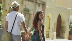 Happy couple walking through village - stock footage