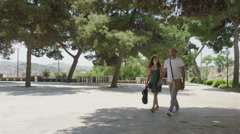 Attractive couple walking through natural outdoor area in small Italian town Stock Footage