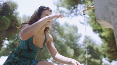 Beautiful woman in the summertime, washing hands in natural green outdoor area - stock footage