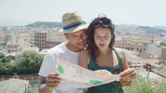 Happy attractive couple on vacation looking at map and taking in the local sight - stock footage