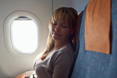people travelling relaxed woman sleeping on plane - stock photo