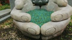 Japanese Buddhist sculpture of giant hands holding marbles Stock Footage
