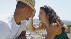Happy attractive couple on vacation share a kiss as they look at the view - stock footage