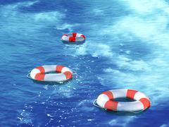 Three lifebuoys, floating on waves - stock photo