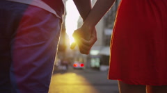 Attractive romantic couple walking through a street in Italian town at sunset - stock footage