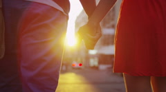 Attractive romantic couple walking through a street in Italian town at sunset Stock Footage