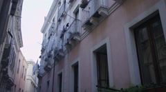 Row of apartments on a narrow Italian street with laundry hanging out do dry Stock Footage