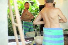 Man in bath towel posing in front of the mirror in bathroom NTSC Stock Footage