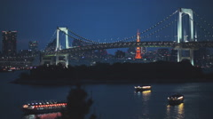 Two famous Tokyo landmarks. The Rainbow Bridge and Tokyo Tower at night Stock Footage
