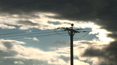 Time lapse of clouds moving past electricity post and wires Stock Footage