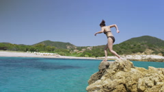 Excited woman on vacation jumping into the clear blue water - stock footage