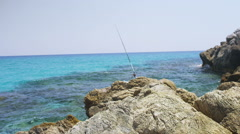 Fishing rod on a rocky outcrop of the mediterranean sea. No people Stock Footage