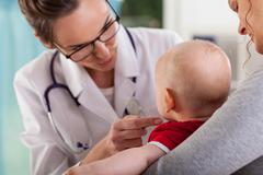 baby boy with mother at doctor's office - stock photo