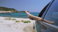 Woman relaxes in a car on the beach with her feet out of the window Stock Footage