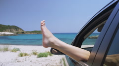 Woman relaxes in a car on the beach with her feet out of the window - stock footage
