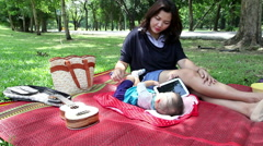 Young asian mother relaxing  with little baby laying in the natural park Stock Footage