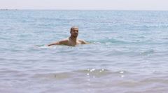 Portrait of attractive man at the beach, relaxing in the water - stock footage
