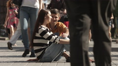 4K & HD resolutions, The lovers sitting on the sidewalk in the crowd stream Stock Footage