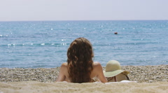 View from behind of woman relaxing alone on the beach - stock footage
