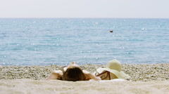 View from behind of woman relaxing alone on the beach Stock Footage