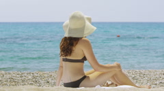 Portrait of a beautiful woman relaxing alone at the beach - stock footage