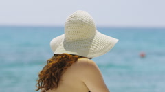 Portrait of a beautiful woman relaxing alone at the beach Stock Footage