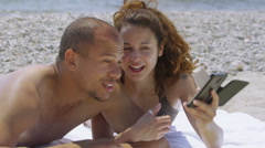 Stock Video Footage of Attractive happy couple relaxing together at the beach with camera phone