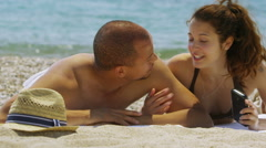 Attractive happy couple relaxing together at the beach with camera phone - stock footage