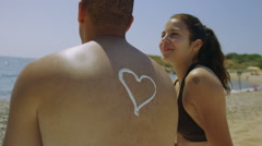 Attractive happy mixed race couple sunbathing together at the beach - stock footage