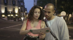 Attractive couple looking at map & trying to find their way around Italian city Stock Footage